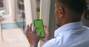 Guy hands using phone with mock up screen. Over shoulder view of afro american man touching and zooming phone green