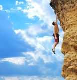 Guy hanging on rock. Muscular guy hanging on the one hand holding rock Royalty Free Stock Photography