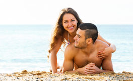 Guy and happy girlfriend laying on sand Stock Photo