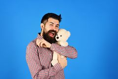 Guy with happy smiling face plays with white soft toy. Childish mood concept. Man holds teddy bear on blue background. Man with beard cuddles with cute toy royalty free stock images