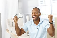 Guy happy winning computer game. Portrait of laughing black guy happy winning computer game at home, holding joystick, raising arms Stock Photo