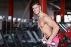 A guy with weights in his hands does exercises on a blurred background of the gym. The guy is hard-nosed with a smile with kettlebells in his hands doing Royalty Free Stock Photos