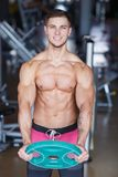 A guy hardened with a smile doing an exercise with a pancake from a bar on a blurred background of the gym. A guy hardened with a smile with a bare torso doing Stock Photography
