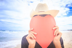 Guy in Hat Hides Face behind Hand-made Red Heart on Beach Stock Photography