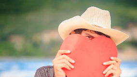 Guy in Hat Holds Red Heart in Front of Face Looks out in one Eye. Closeup European guy in nice white hat holds hand-made large red heart in front of face looks stock footage