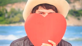 Guy in Hat Holds Red Heart in Front of Face Turns Head Smiles stock video footage