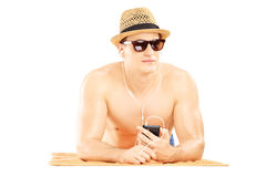 Guy with hat and sunglasses lying on a towel and listening music Stock Photos