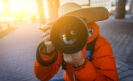 Guy in hat takes pictures. With camera on street Stock Images