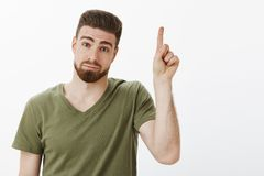 Guy have one suggestion raising index finger add idea standing silly and cute with hesitant and shy expression pouting. Tilting head and looking at camera with stock image
