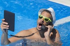 Guy having a call from a swimming pool Royalty Free Stock Photography