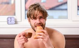 Guy having coffee and holds croissant while lay bed in bedroom or hotel room. Bearded man in bed drinking morning royalty free stock image