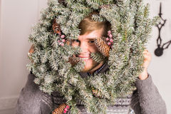 Guy having fun at party. Man with a Christmas wreath on his face Concept of a fun party on Christmas or the New year Royalty Free Stock Photo