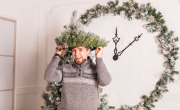 Guy having fun at party. Man with a Christmas wreath on his head. Concept of a fun party on Christmas or the New year Stock Image