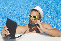 Guy having an internet call from the swimming pool. Young man having an internet call at the swimming pool edge. He is using tablet device and retro styled Stock Image