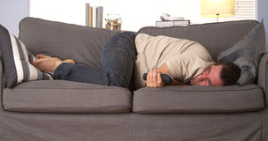 Guy having trouble sleeping. On couch a home Stock Image