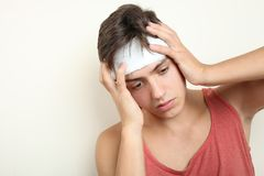 A guy with a head injury. On a neutral background. Concept first medical aid stock photos