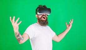 Guy with head mounted display interact in VR. Man with beard in VR glasses, green background. Power concept. Hipster on stock photography