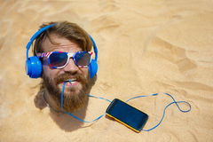 Guy with headphones. Buried in the sand on the head royalty free stock photography