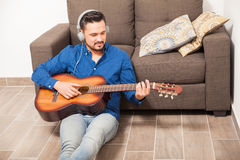Guy with headphones playing the guitar at home Royalty Free Stock Photo