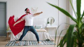 Guy in headphones wearing super hero costume red cape and mask dancing at home. Guy in headphones wearing super hero costume red cape and mask is dancing at home stock video footage