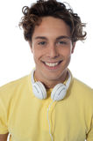 Guy with headsets around his neck smiling at you Stock Photo