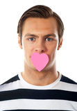 Guy with heart shaped paper on his mouth Stock Photography