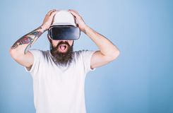 Guy in helmet works as engineer in virtual reality. 3D design concept. Man with beard in VR glasses shocked and. Disappointed, light blue background. Architect stock images