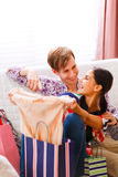 Guy helping her girlfriend to choose dress Royalty Free Stock Image