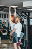 Guy hepl girlfriend on training in gym Royalty Free Stock Images