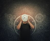 Guy hiding face holding a clock instead of head stands over dark blackboard with drawn gears and cogwheels stock photography