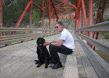 Guy and his dog. Pausing after a walk in the country Stock Images