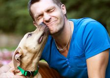 Guy with his dog hugging in the park Stock Photography