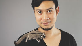 A guy with his exotic pet. An asian man with black t-shirt royalty free stock images