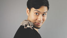 A guy with his exotic pet on his shoulder. An asian man with black t-shirt stock image