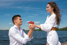 The guy is on his knees before the girl on a wooden pier near th Royalty Free Stock Photos