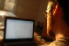 Guy at his laptop computer. Bearded young man with glasses looks at his laptop tomputer Stock Photos