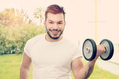 Guy holding barbells warm filter applied Royalty Free Stock Photo
