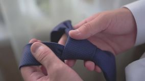 The guy is holding a blue tie. Stylish men`s accessory. Close up. Evening men`s fees stock video