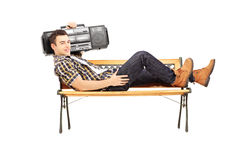 Guy holding a boombox on his shoulder and lying on a bench Stock Photography