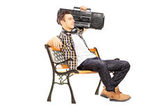 Guy holding a boombox on his shoulder and sitting on a wooden be Stock Image