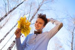 Guy holding bouquet of autumn leaves Royalty Free Stock Photo