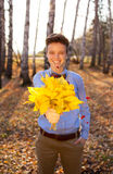 Guy holding bouquet of autumn leaves Stock Photo