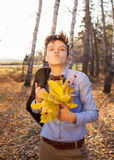 Guy holding bouquet of autumn leaves Royalty Free Stock Images
