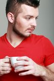 Guy holding coffee cup. Portrait of handsome guy holding coffee cup Royalty Free Stock Photography