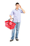 Guy holding an empty shopping basket Royalty Free Stock Photo