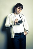 Guy holding the film camera. Photographer holding  the film camera on light background. Contrast image Royalty Free Stock Photos