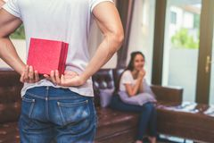 Guy holding gift behind him for surprise his waiting girlfriend at their home. Selective focus on gift.  royalty free stock image