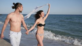 Guy holding girl by hand, walking barefoot on sand, couple in love, an exotic vacation, on background beach panorama. Summer, slow motion, love, romantic walk stock video footage