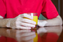 Guy holding glass of juice. Close-up of man in red t-shirt holding glass of orange juice Stock Image