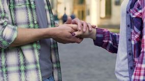 Guy holding hand of girl and stroking it, university sweethearts, first love. Stock footage stock video footage